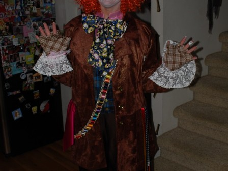 Mad Hatter costume, enhanced with lace cuffs, plaid mitts, ribbon streamers, hot pink satin hankie and a thread bandolier.